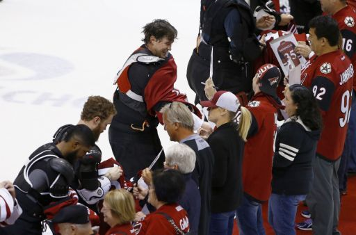 Arizona Coyotes' Anthony Duclair, left, Max Domi, second from left, and Shane Doan, middle, give their game jerseys to fans after the team's NHL hockey game against the Minnesota Wild on Saturday, April 8, 2017, in Glendale, Ariz. The Wild defeated the Coyotes 3-1. (AP Photo/Ross D. Franklin)