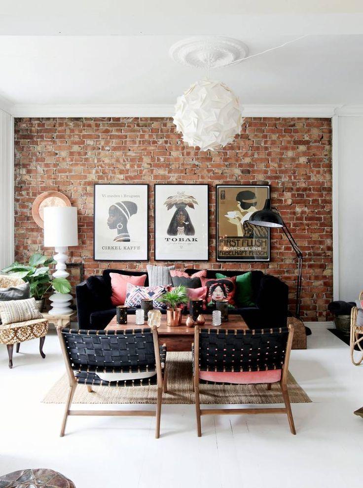 BOHEMSK:Ved å møysommelig grave seg frem til stuens opprinnelige murvegg skapes en urban og røff stil, som balanseres av den myke fløyelssofaen fra Ikea, full av puter i korall og grønt. Lenestolene med flettet skinn er fra Hübsch, og den lille Emma-stolen er arvet. Stuebordet er kjøpt på Bohus for ti år siden. Plakatene fra nettbutikken Perchs Thehandel gir ytterligere særpreg til stuen. Taklampe fra Habitat, hvit stålampe fra HK Living og XXL gulvlampe fra Kremmerhuset.