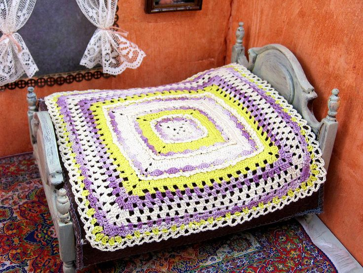 Miniature dollhouse crochet bedspread features granny square styling.