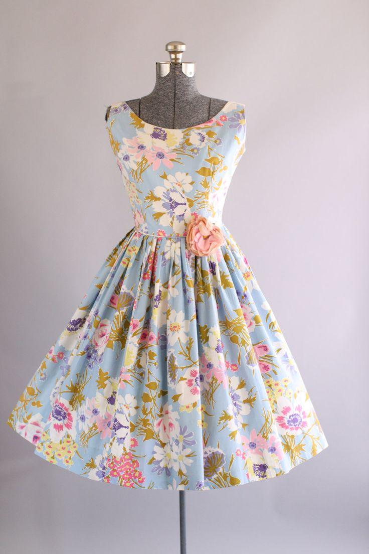 Deze jaren 1950 katoenen jurk beschikt over een prachtige bloemenprint bovenop een licht blauwe achtergrond. Mouwloos. Gesmoord taille. Vrij