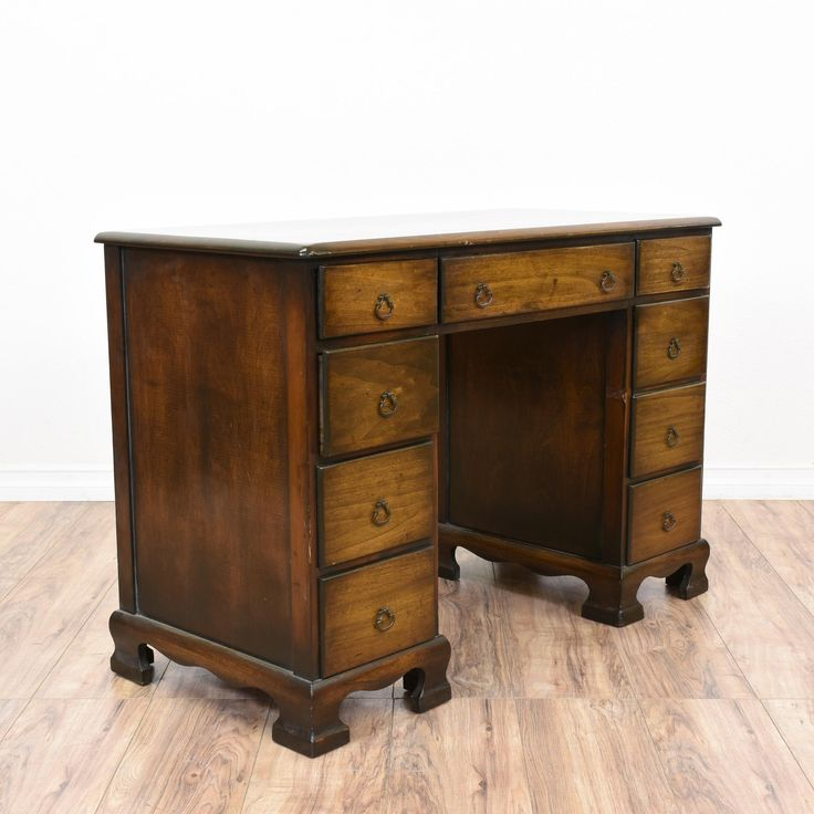 This kneehole desk is featured in a solid wood with a glossy dark walnut finish. This traditional desk is in great condition with 9 large drawers, carved legs and curved trim. Perfect for storing paperwork and books! #traditional #desks #kneeholedesk #sandiegovintage #vintagefurniture