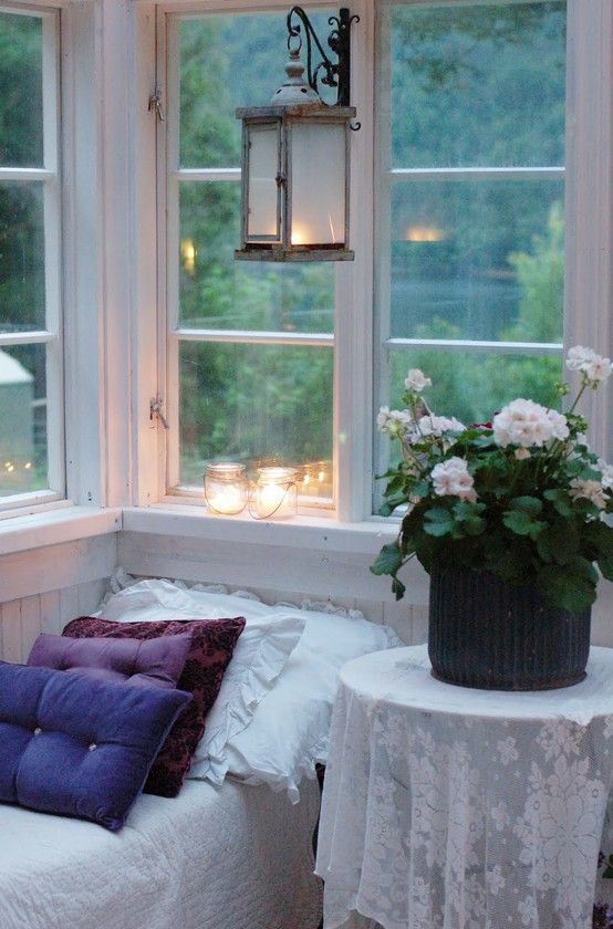 white wood porch with geranium and a view to water