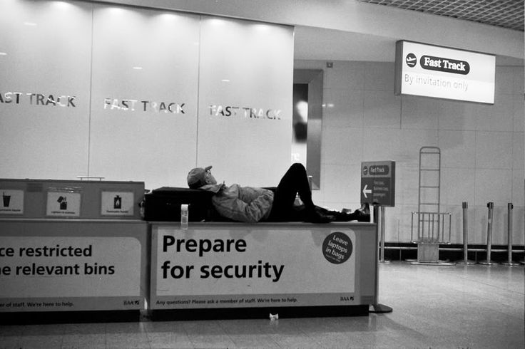A Man Sleeping on the Security Counter at Heathrow Airport, London, England