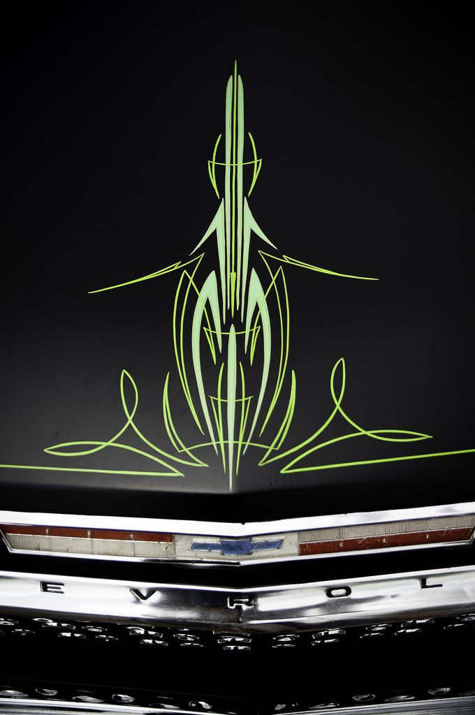 Green pin stripes on the centerline of a black car hood....