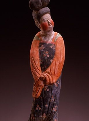 Lady with chignon in a floral dress -funerary statuette. Tang Dynasty (618-907). Terracotta, clear slip and polychrome.