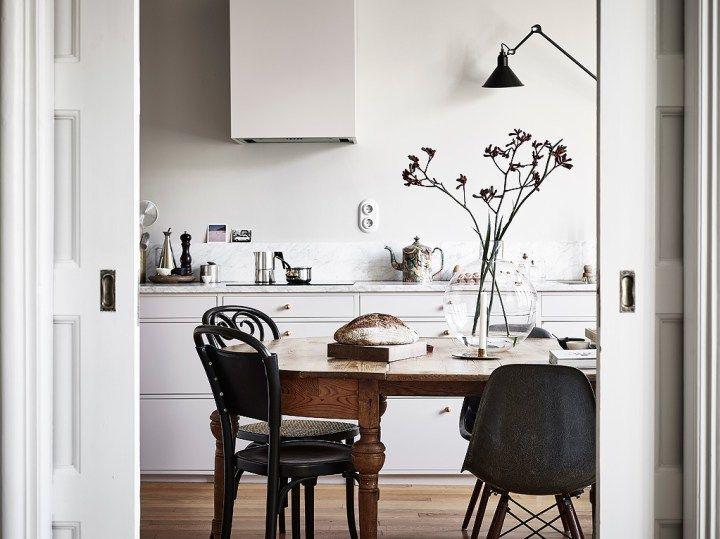 Mezcla de sillas negras, Thonet y Eames, acompañando una mesa de madera en una cocina nórdica de color blanco