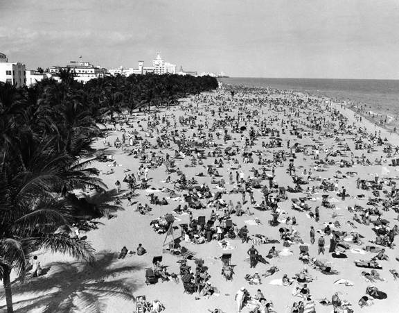 Miami Beach Packed With Sunbathers, circa 1940 - On the sands of Miami Beach's Lummus Park, no clue is visible that a nation and the world were just emerging from the worst depression in history. Looking north from the Shoreham-Norman Hotel on February 10, 1940, it is evident that everybody who could afford to escape the brutal northern winters would, if they were able, come to Miami Beach.     Photo and caption provided courtesy of Historic Photos of Greater Miami. (Miami Beach, Florida)