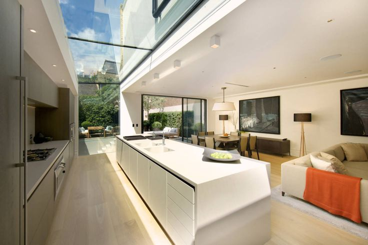 Kitchen and sitting area with views of the back garden at Bedford Gardens house. : Modern kitchen by Nash Baker Architects Ltd