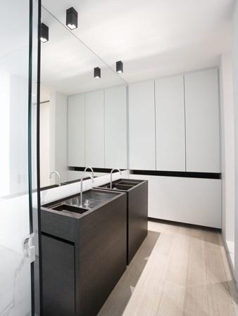 Lavabogedeelte in de badkamer met 2 vrijstaande lavabomeubels in donker hout (contrasteert mooi met de rest van de badkamer in het wit). Naast de lavabo's is nog extra opbergruimte voorzien voor handdoeken e.d.