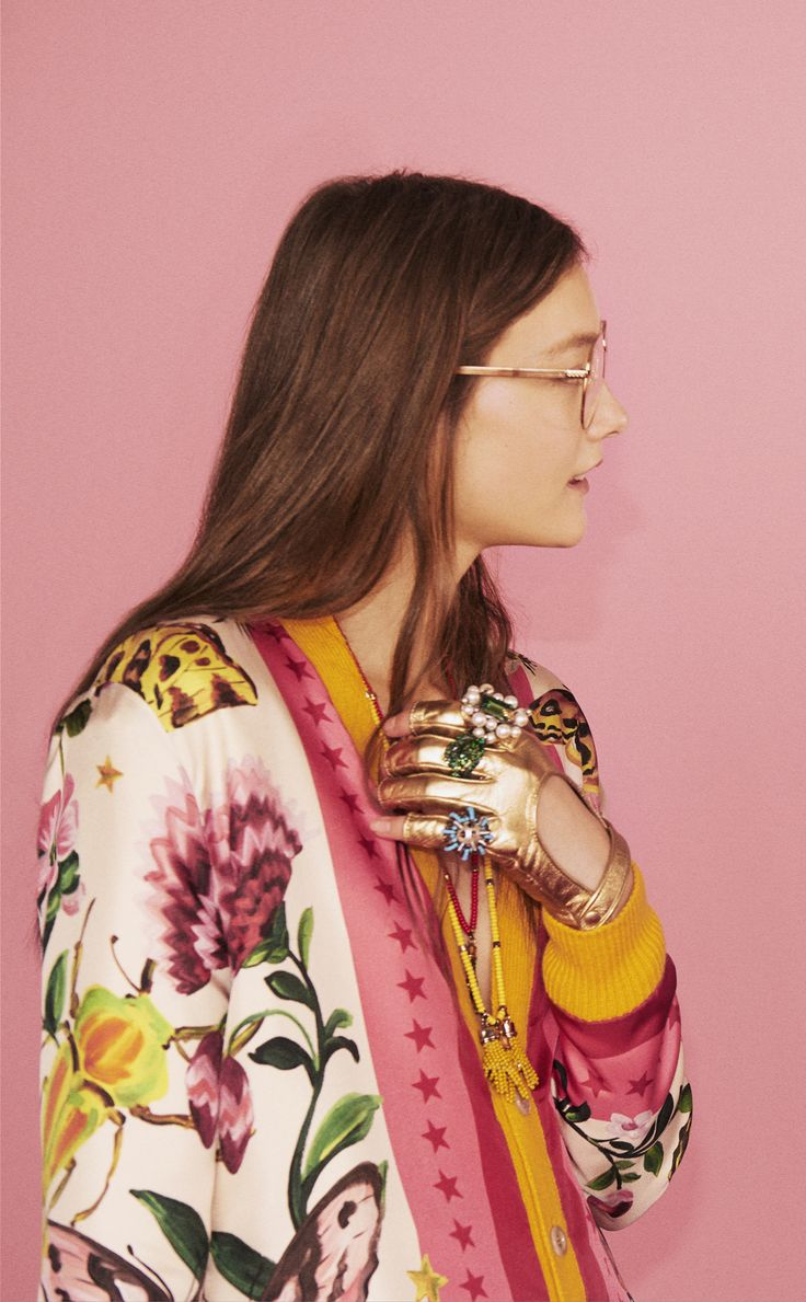 Looks from the Gucci Garden capsule collection. A reversible printed silk and wool-cashmere cardigan with metallic leather fingerless gloves in light gold, complemented by an array of bold rings.