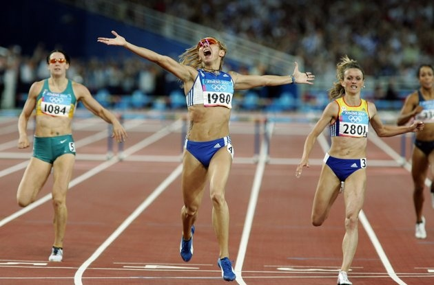 Inspirational Moments: Olympic celebrations - ATHENS - AUGUST 25: Fani Halkia of Greece crosses the finish line in first place in the women's 400 metre hurdle final, with Jana Pittman (left) of Australia finishing fifth and Ionela Tirlea-Manolache (r) of Romania finishing second on August 25, 2004 during the Athens 2004 Summer Olympic Games at the Olympic Stadium in the Sports Complex in Athens, Greece. (Photo by Stuart Hannagan/Getty Images)