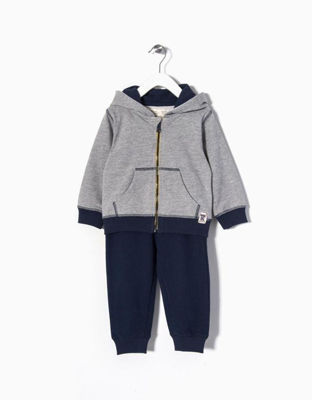 Fato de treino para bebé menino. Casaco com capuz e estampado nas costas. Calças com cintura elástica.
