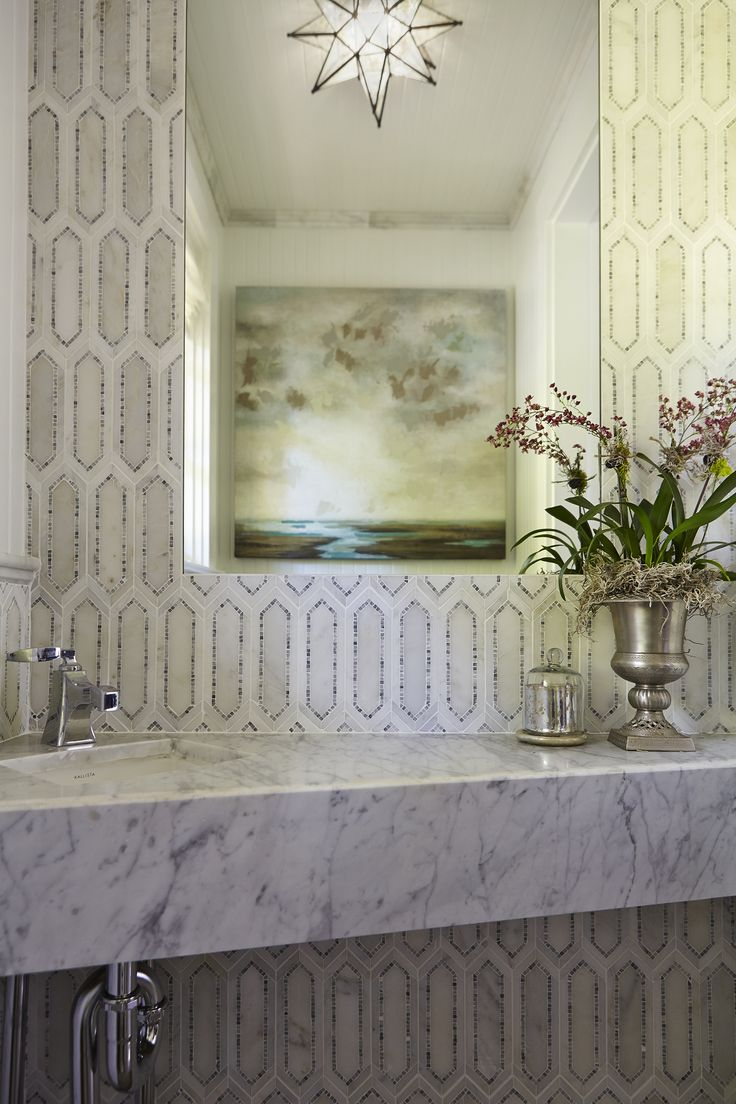 In the Powder Room, a crystal light fixture from Ballard Designs and plenty of marble bring the glam. Walls are made with tile from AKDO, which are marble with stone inlay - Traditional Home® / Photo: John Merkl / Design: NV Design Studio