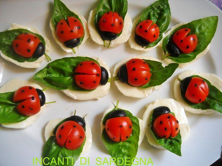 Marienkäfer aus Tomate und Morzarella auf Basilikumblatt Ladybird mozzarella, basil, tomato, black olive