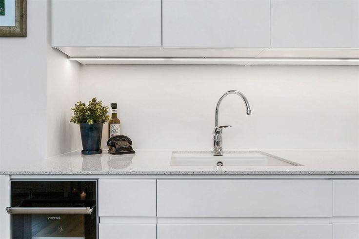 Kjøkken fra Drømmekjøkkenet med granitt benkeplate med underlimt oppvaskkum og LED lys under kjøkkenskap.