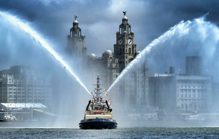 """The Tug-boat """"Svitzer Stanlow"""" firing it's water canon in salute in front of the Royal Liver Building's."""
