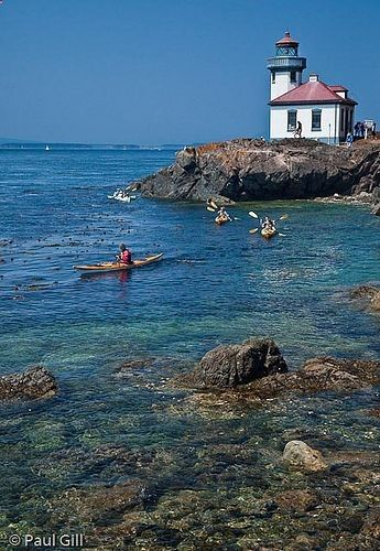 Kayakers paddling near the lighthouse, Lime Kiln Point State Park, San Juan Island, Washington