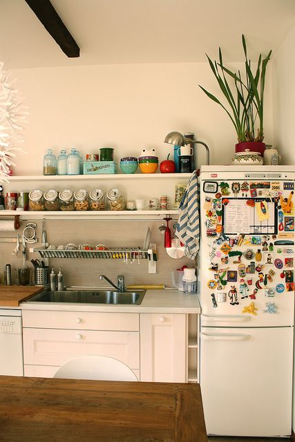 """I love how this kitchen feels """"real"""" with the magnets on the fridge, dishtowels, etc yet still looks stylish. Love that above the sink drainage too."""
