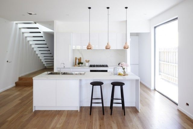 Kitchen: gloss white handleless cabinets, white stone benchtops, copper pendant lights, marble splashback, black bar stools, minimalist staircase