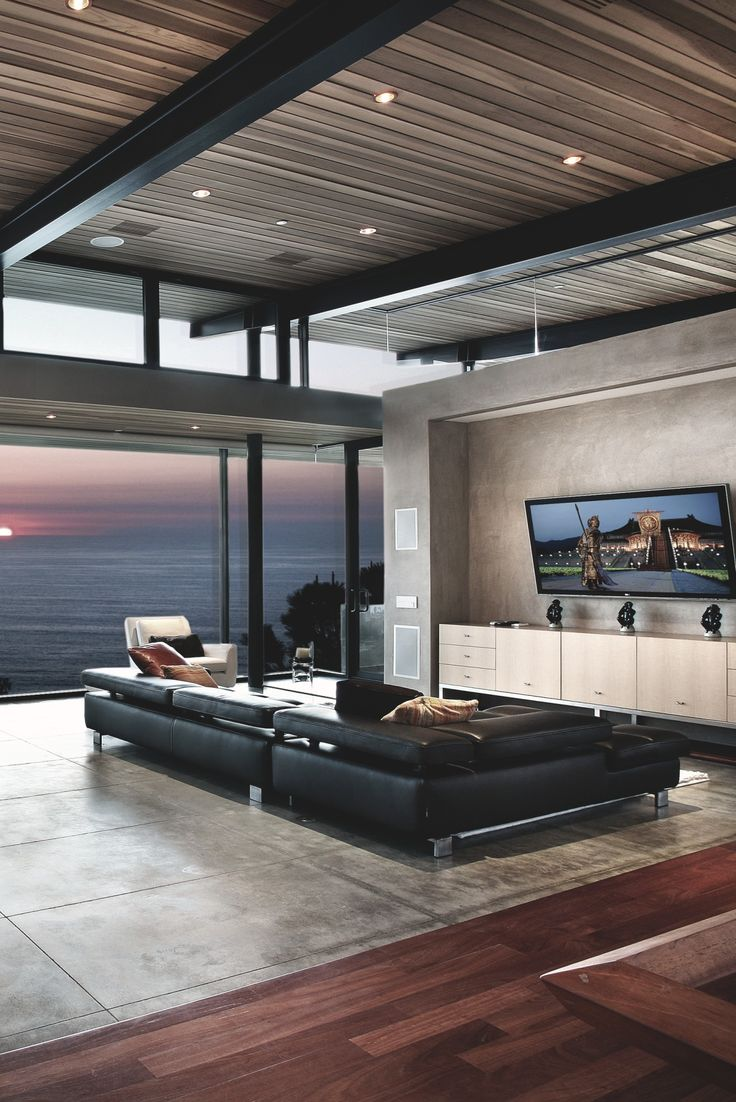 Living room: Grey marble/ wooden floors, ocean view, low lying black couch and flat screen TV