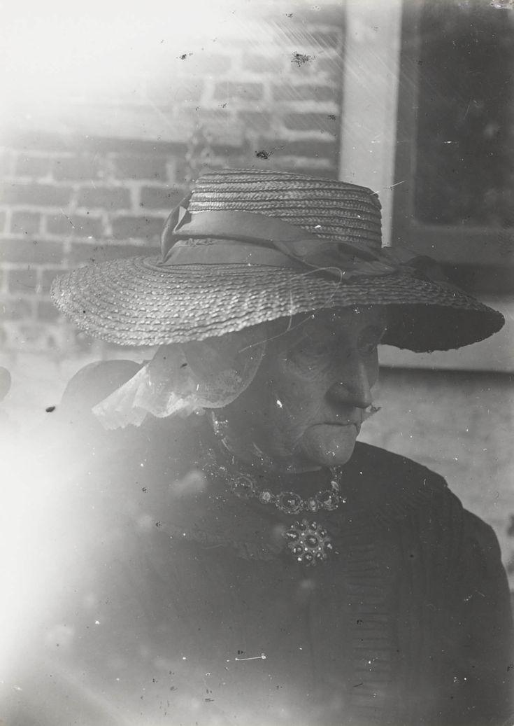 Vrouw in Friese streekdracht. De vrouw draagt een strohoed over de muts en het oorijzer. 1913-1916 #Friesland