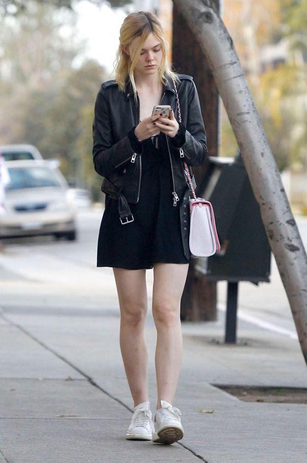 Elle Fanning em look all black com jaqueta biker de couro e tênis branco