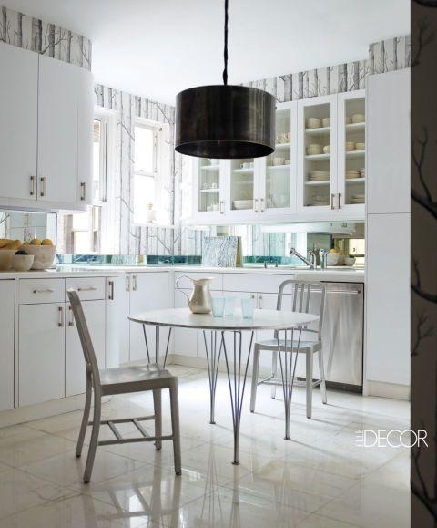 En la cocina, una lámpara industrial vendimia se suspende sobre una mesa de 1960 rodeada de sillas Emeco;  el hardware de gabinetes es por Restoration Hardware, el lavavajillas es de LG, el fondo de pantalla es por Cole & amp;  Hijo, y el suelo es de mármol Calacatta.