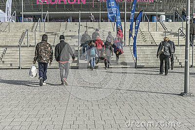 Concrete stairs  to the Sports Hall Tauron arena in Krakow , Poland . And people going to the Tauron arena .