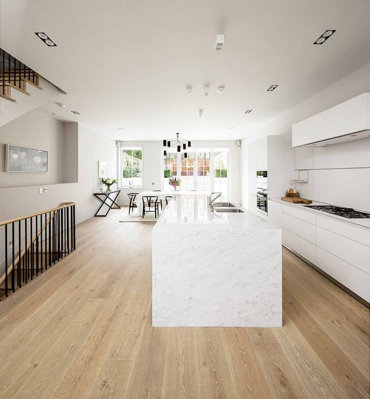 Open concept all white kitchen and dining space with light hardwood floors and marble center island