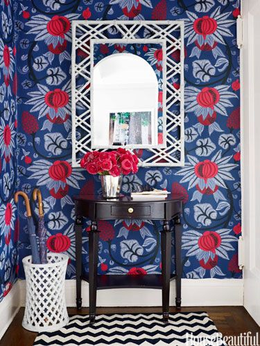 """Entry Whittaker chose Osborne & Little's Maharani wallpaper for the entry: """"Billy Baldwin said you should start with a dark space and work your way through the apartment, lightening rooms as you go."""" The Ballard Designs table allows just enough clearance to open the front door. Bungalow 5 mirror. Stephanie Odegard umbrella stand."""