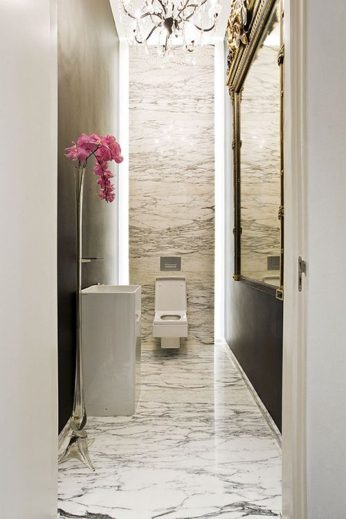 Bathroom Design Tips In long and narrow #bathroom create more visual space by extending the flooring all the way up to the walls. Marble and a big mirror will give a fine touch!  #bathroomdesign #bathroommarble #bathroomremodeling