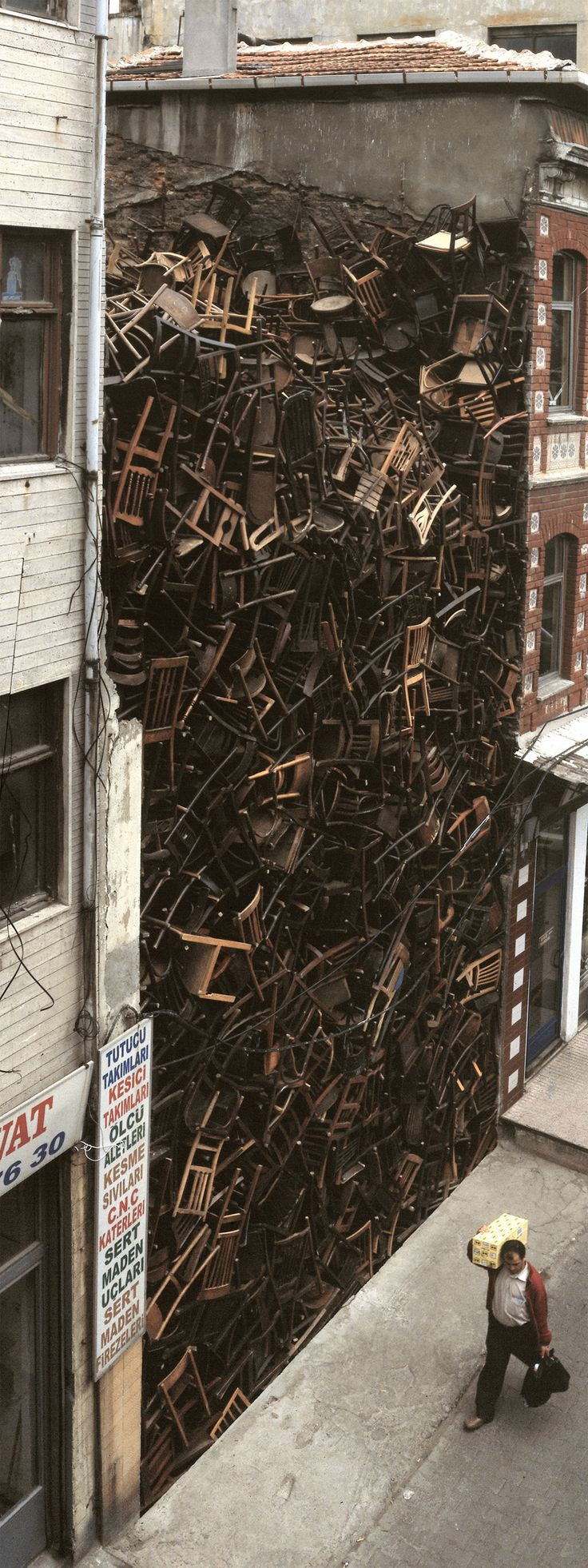 Doris Salcedo. 1,550 wooden chairs piled high between two buildings in central Istanbul. -wtf?? Why lol