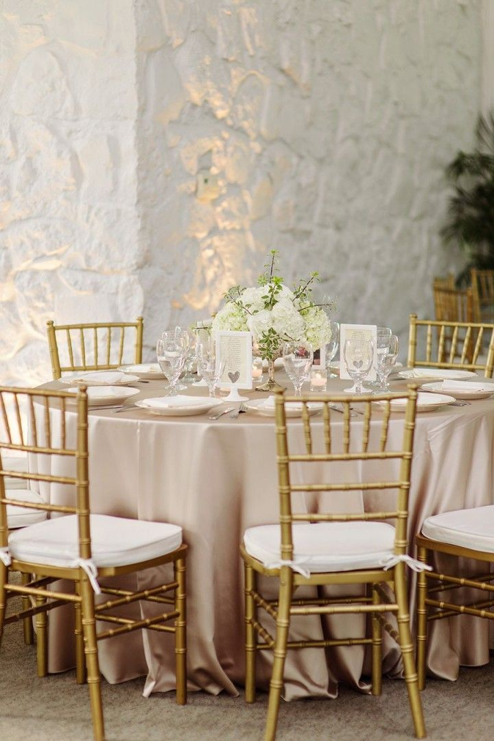 Ivory linen guest tables with gold chivaris.                                                                                                                                                                                 More