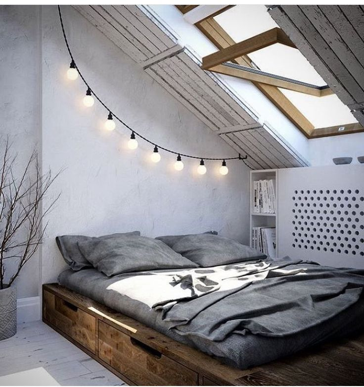 zoiets misschien voor in de logeerkamer... Attic in a barn feel. slanted ceiling, italian lights, dark wood baseboard with storage, sky light, wood paneling, secret book storage, gray, grey, white wash, whitewash,