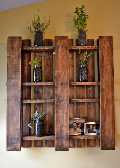 DIY home furniture by hanging a pallet to display your photos and plants #DIY #pallet