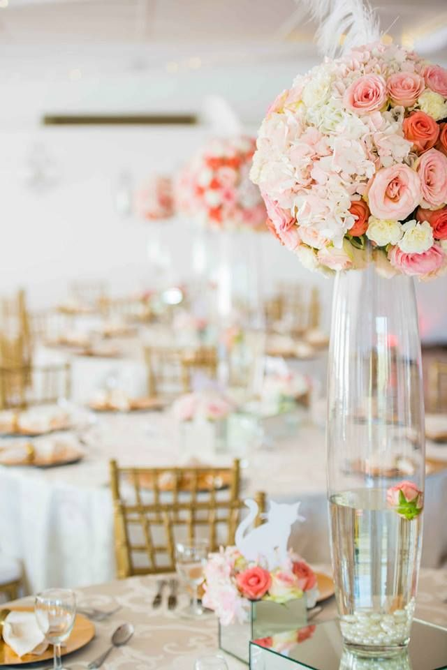 Monte Vista Venue peach and gold centerpiece with a medium arrangement on top of the bullet vase with a feather in, a single rose floating in the vase, white pebbles at the bottom of the vase, all on a mirror box.