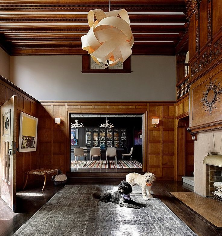 Historic interior with wood on floor, wainscoting and ceiling, combined with modern furniture and interesting light fixtures