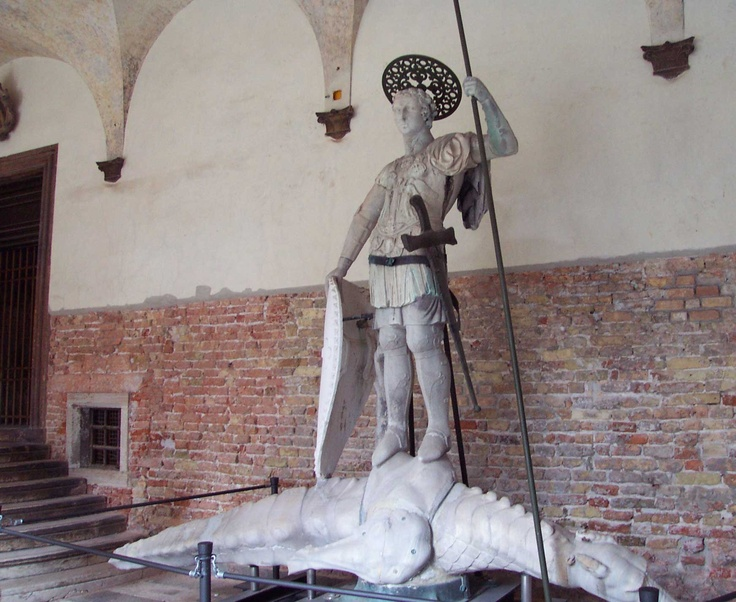 St. Theodore: original statue -- Doges' Palace, Venice, Italy    The statue of Theodore that stands atop the column on the Piazzetta is a replica of this one, which is now in a protected area of the Ducal Palace. The original body of the statue is Hellenistic, and appears to be that of a soldier. Here is another example of the alteration of an earlier, pagan work of art to make it Christian. The Hellenistic statue was given a shield, sword, staff, and halo to make him Theodore, defender…