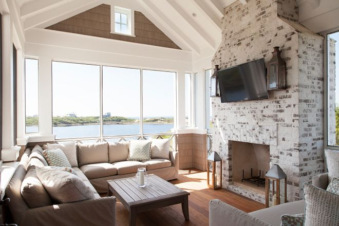 Now this is a screen porch, with the fireplace and the TV, the comfortable seating and the game table who would not use this room. Shingle Style Beach House with Classic Coastal Interiors