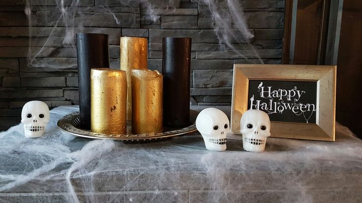 """Fireplace covered with some spiderweb, candels, sculls and """"Happy Halloween"""" sign."""