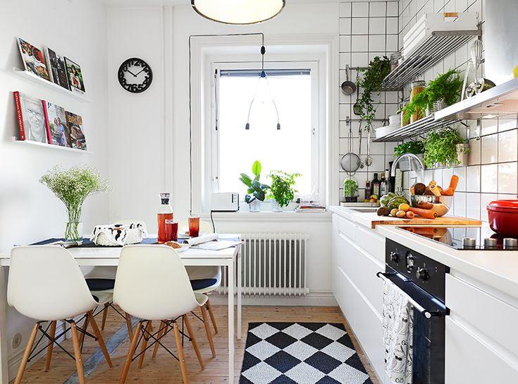 Mooie kuipstoeltjes voor in de keuken, en veel plantjes! Tijdschriftenplank boven de tafel is ook gaaf.