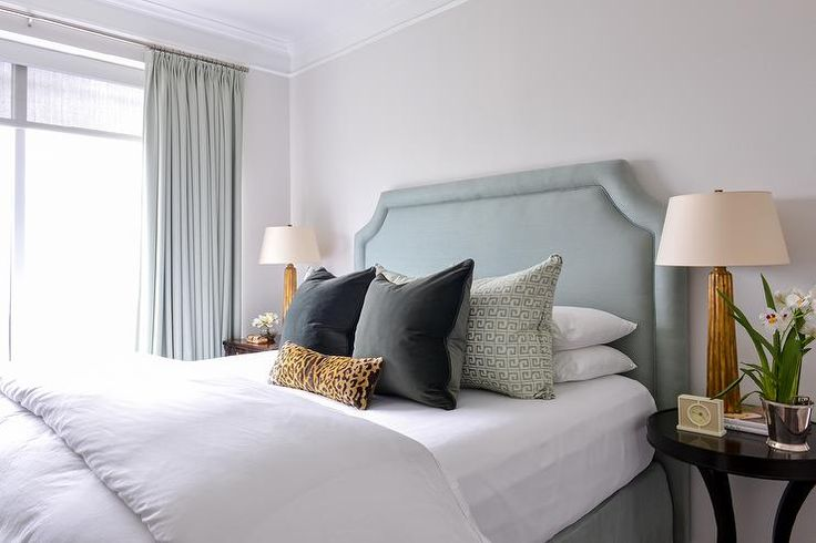 Beautiful bedroom features a blue velvet headboard on bed with matching bedskirt as well as crisp white bedding, two tone velvet pillows and a leopard print lumbar pillow flanked by round black bedside tables and gold leaf rippled lamps.