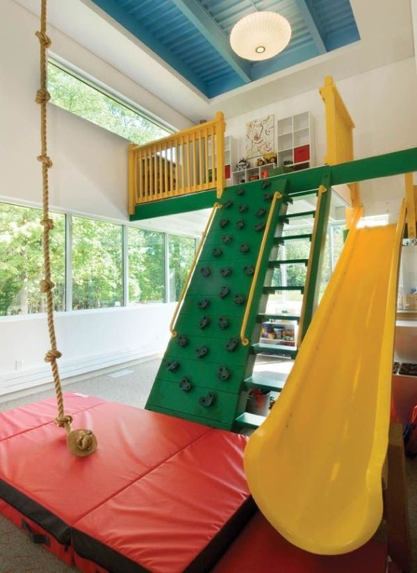 At the end of a hall in this home is a 14x22-foot #playroom that includes an indoor jungle gym, rock climbing wall, rope swing and a door to the deck.