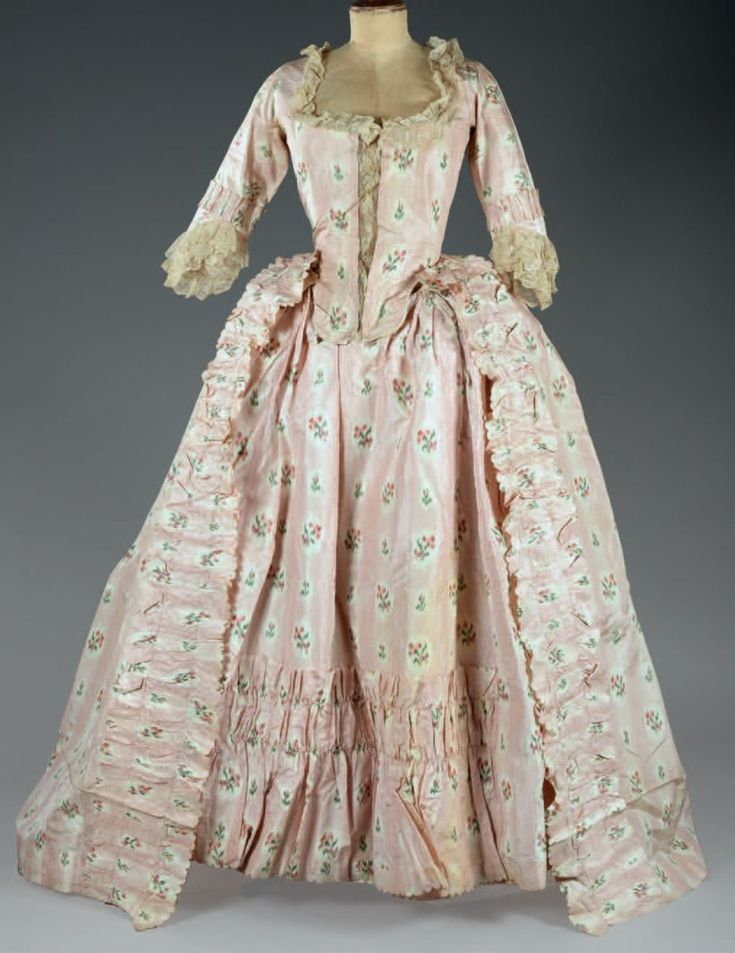 ca 1760 robe a l'francais of pink silk taffeta with floral sprays, transformed into a robe a l'anglaise under Louis XVI. Laced bodice and straight half long sleeves, round neckline highlighted w/Valenciennes lace. Pleated flounces on front opening sides of full skirt and hem of petticoat.