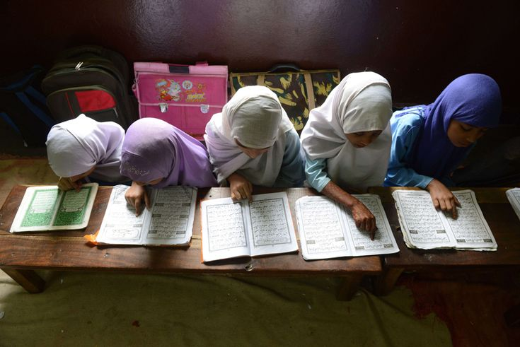 Indian Muslim girls recite the Holy Quran in their class room during the holy…