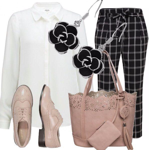 Pantaloni a quadrettoni bianchi e neri indossati con una camicia bianca di taglio classico, scarpe stringate rosa pallido e borsa uguale, fiori neri come orecchini.