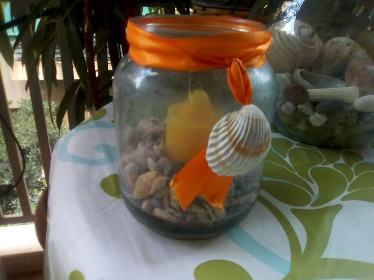 Jar with sea shells and candle for the veranda table