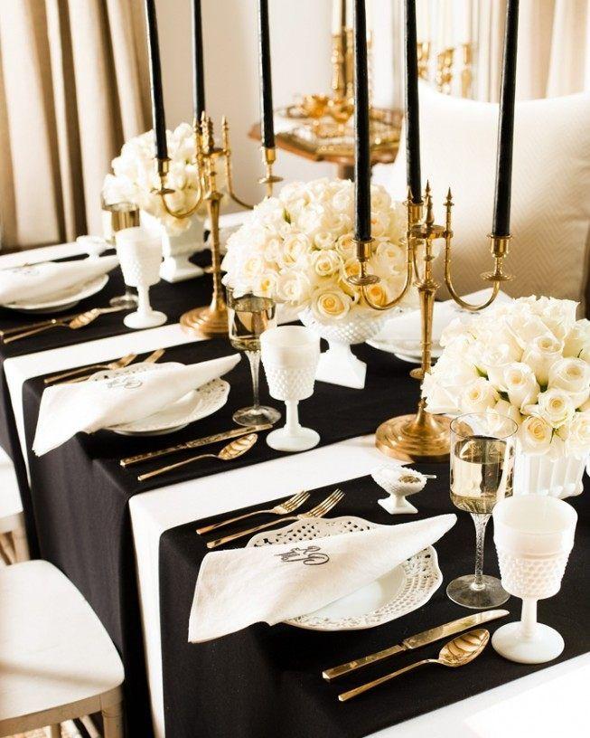 schwarze Tischläufer, weiße Blumengestecke und goldene Kerzenständer