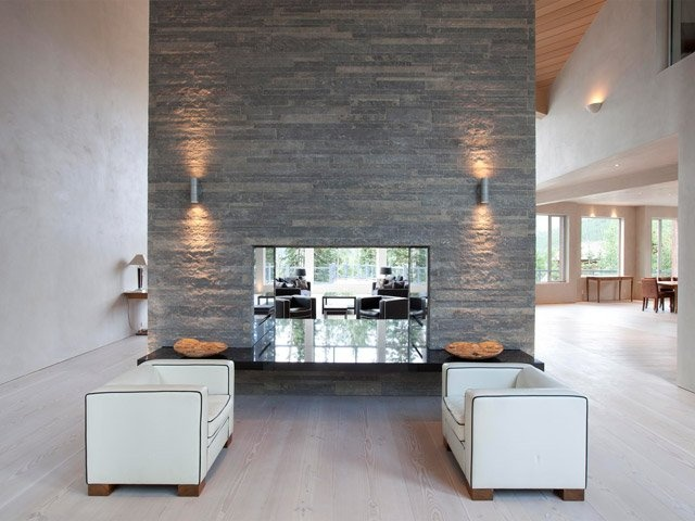The foyer has a black granite fireplace with floor-to-ceiling hand-cut limestone.