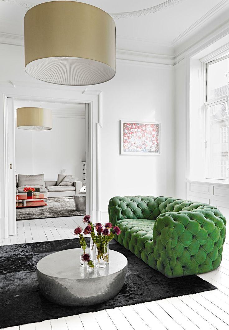 Den mörka mattan kontrasterar mot de vita väggarna och golvet, medan den gröna soffan adderar liv och mjukar upp intrycket. Notera skillnaden i stämning i det angränsande rummet med soffa och matta i beige!